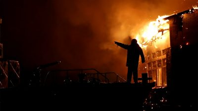 House building on fire at night. Inferno conflagration. Fireman fights fire.