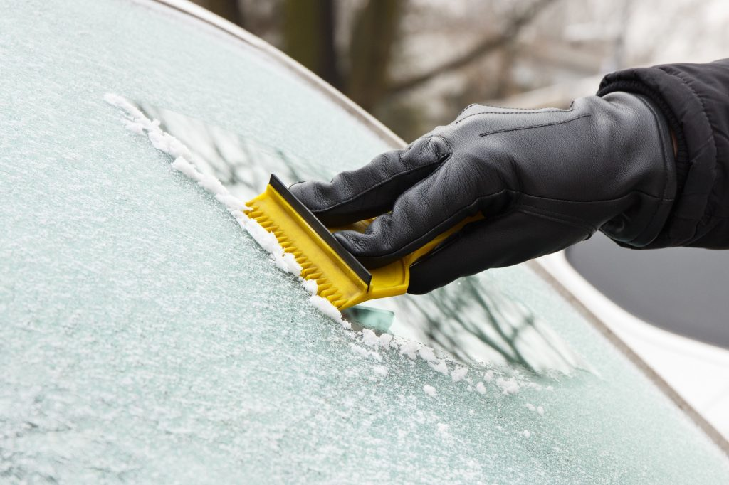 Hand in leather glove scraping ice or snow from window of car
