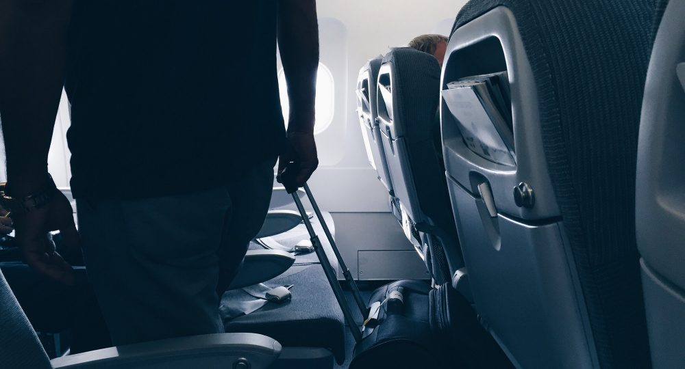 Passenger on board, in flight, silhouette with luggage, seats and window, sunlight, departure