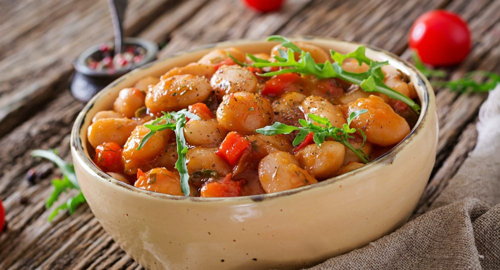 Steamed white beans with vegetables in tomato sauce. Vegan food. Asian meal.