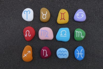 Astrological chinese signs painted and graved on stones over black volcanic sand
