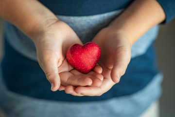 Child holding red heart in his little hands