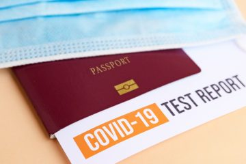 Close-up image of passport with covid test report.