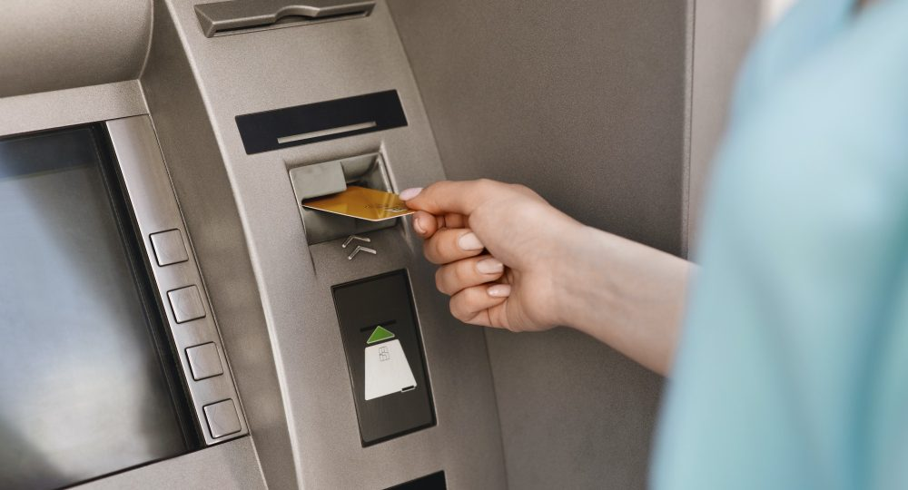 Close up of female hand inserting credit card in the ATM machine
