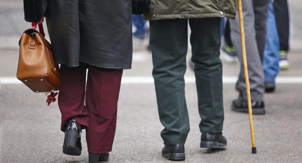 Elderly people croosing a street. Pensioner, adult care. Horizontal