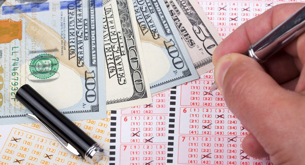 Lottery tickets with a pen and American Dollars