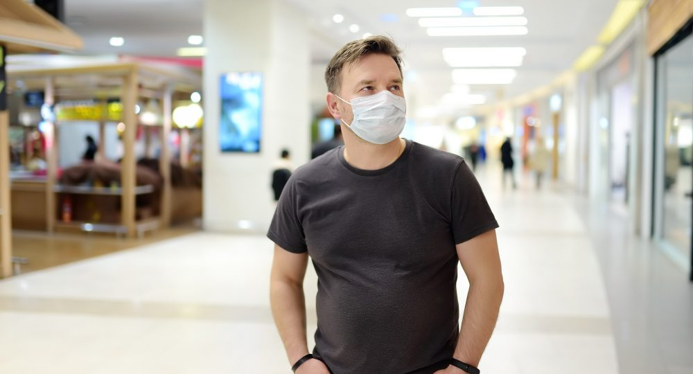 Man in face mask in airport or supermarket or other public place during coronavirus epidemic. Safety