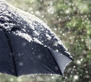 Snow flakes falling on a black umbrella
