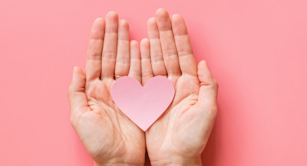 Valentine's day background. Female hands holding pink hearth. Flat lay, top view, mockup, template