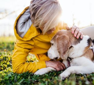 Front view of senior woman lying on grass in spring, petting pet dog