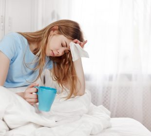 A sick girl with a headache is sitting under a blanket on the bed in the bedroom