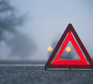 Traffic problem in thick fog. Car on the road behind warning triangle.